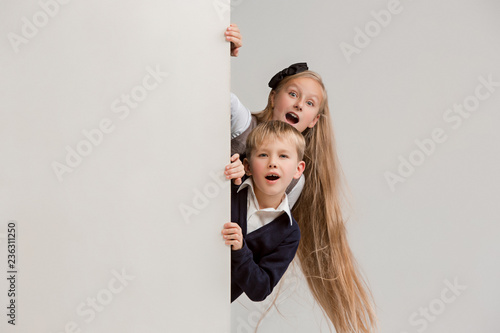 6f38268510 Banner with a surprised children peeking at the edge with copyspace. The  portrait of cute little kids boy and girls ...