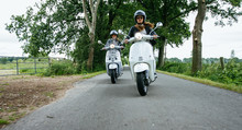 Young Girls Riding Scooter On Rural Road