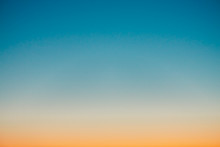 Predawn Clear Sky With Orange Horizon And Blue Atmosphere. Smooth Orange Blue Gradient Of Dawn Sky. Background Of Beginning Of Day. Heaven At Early Morning With Copy Space. Sunset, Sunrise Backdrop.