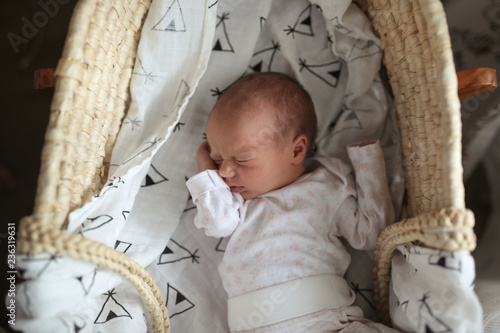 Vászonkép newborn sleeps in wicker crib on muslin diaper