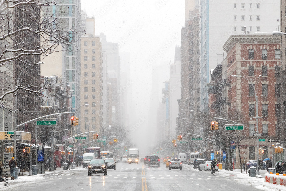 Fototapety, obrazy: Snowy winter street scene looking down 3rd Avenue in the East Village of Manhattan during a nor'easter snowstorm in New York City