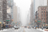 Fototapeta Nowy Jork - Snowy winter street scene looking down 3rd Avenue in the East Village of Manhattan during a nor'easter snowstorm in New York City