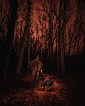 Person In Wizard Costume Carrying Man Between Murk Forest In Redness