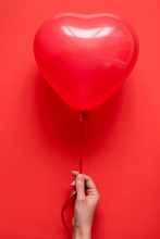 Hand Holding A Red Heart Balloons On Red Paper Background. Valentine's Day Or Birthday Celebration Concept