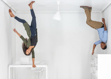 A Young Couple Hanging Upside Down In An Office
