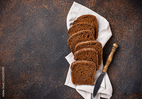 Staande foto Brood Fresh sliced rye bread on rusty background