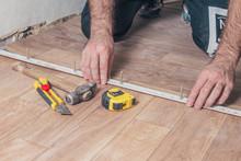 Minsk, Belarus - November 12, 2018: Installation Of Self-adhesive Plastic Floor Threshold Sill By MYCK When Docking Floor Coverings