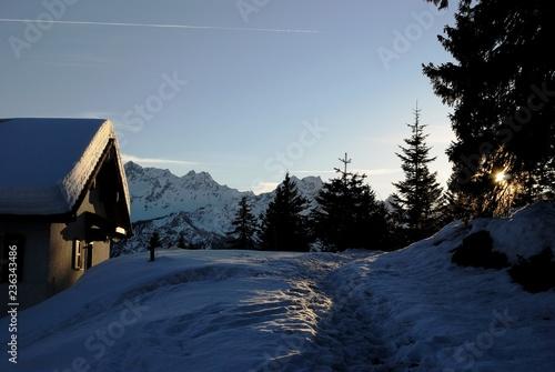 Cabina al tramonto con neve e raggio di sole