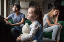 Upset Frustrated Little Girl Tired Of Parent Fight, Toddler Daughter Holding Toy Dreaming That Family Conflicts Would Stop, Suffering From Mother And Father Quarrels, Bad Family Relationship, Break Up