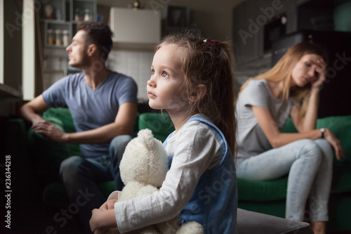 Fotografía  Upset frustrated little girl tired of parent fight, toddler daughter holding toy