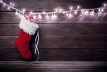 Santa Stocking With Gift Boxes On Wooden Background.