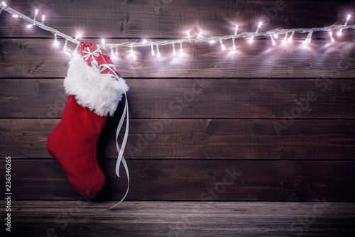 Fotografie, Obraz Santa stocking with gift boxes on wooden background.