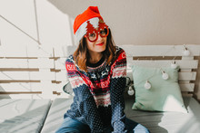.Sweet And Cheerful Woman Enjoying Christmas At Her Home. Wearing Christmas Costume With A Santa Claus Red Hat And Chrismtas Tree Glasses. Lifestyle.