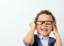 Little Boy Trying A Pair Of Glasses On Stock Photo