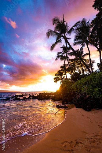 Fototapeta Footprints in the Sand with Awesome Colorful Sky at Sunset and Calm Ocean Water Coming on Sandy Beach Shore with Palm Trees Silhouette and Lush Greenery at Secret Beach in Maui Hawaii obraz na płótnie