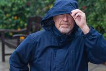 Portrait Of Covered Senior Man Outside In The Rain Wearing Hood And Rain Coat