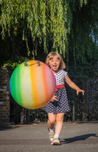 Little Girl Chasing Colorful B...