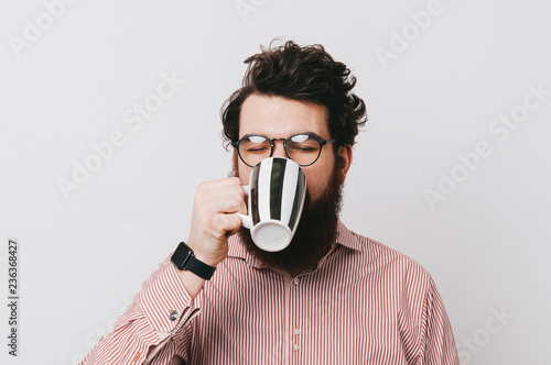Young stylish bearded man drinking and enjoying his mug of coffee, or tea, or hot chocolate Fototapeta