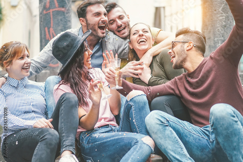 Obraz Happy friends doing party drinking champagne at sunset outdoor - Young millennial people having fun celebrating birthday and laughing together - Friendship and youth holidays lifestyle concept - fototapety do salonu