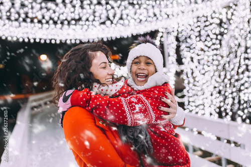Little black girl enjoying in ice skating with her mother. Canvas Print