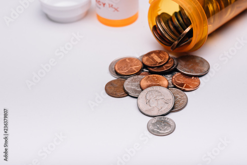 Fotografia  money and pills in pill bottle and stethoscope on table medical expense concept