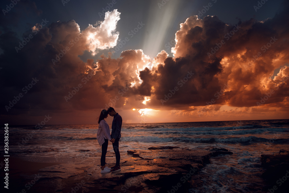 Fototapeta Couple in love at a fiery sunset.Silhouette photo