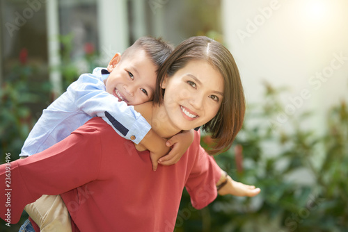 Young Asian woman giving piggyback ride to her little son Canvas Print
