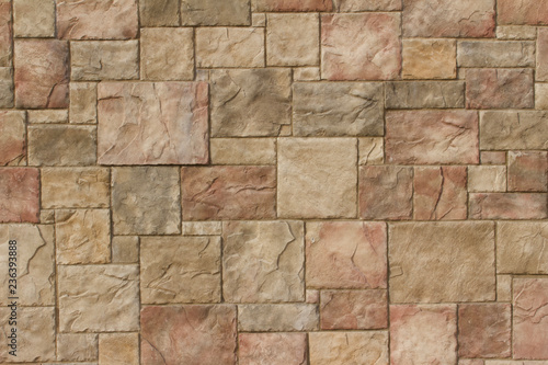 Textured marble look stone wall abstract background in shades of tan, brown and red