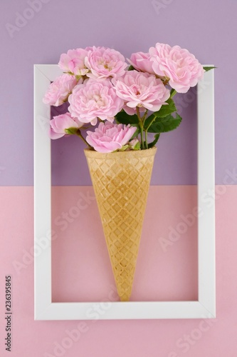 Foto op Canvas Bloemen Floral card in pastel colors.Flower ice cream. Pink roses in a waffle cup in a white frame on the pink purple background.Mother's Day, March 8th greeting card