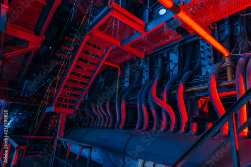 Inside of old abandoned factory. Rusty ruined industrial pipeline connection. Abstract red illuminated industrial background