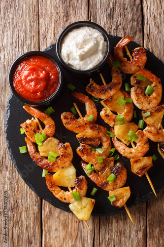 Grilled kebabs with shrimp with fresh pineapples and green onions served with sauces close-up on a slate plate. Vertical top view