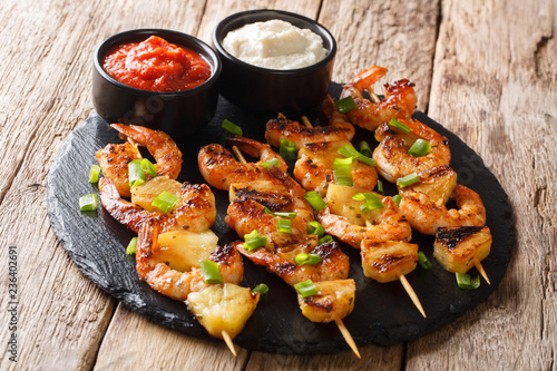 simple homemade recipe for grilled kebabs from shrimp and pineapple slices with sauces close-up on a slate plate. horizontal