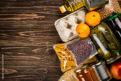 Fotografia  Food donations in box in kitchen background, copy space