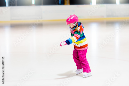 Child skating on indoor ice rink. Kids skate.