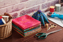 Stack Of Colorful Fabrics On Table Surrounded By Sewing Accessories On Brick Wall Background