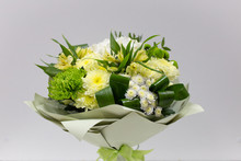 Bouquet Of Fresh Flowers (yellow Green) In Paper Packaging On A Light Background
