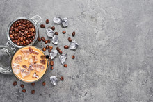 Chocolate, Vanilla, Caramel Or Cinnamon Iced Coffee In Tall Glass. Cold Brewed Iced Coffee In Glass And Coffee Beans In Glass Jar On Grey Concrete Background. Top View With Copy Space For Text.