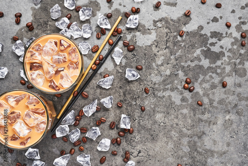Cold brewed iced coffee in tall glass with ice and coffee beans on wet grey concrete background Fototapet