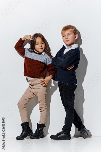 6f8e81057 The portrait of cute little kids boy and girl in stylish jeans clothes  looking at camera against white studio wall. Kids fashion and happy  emotions .