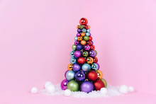 Christmas Tree Made Of Ball Decoration On Pink Background.