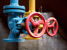 Two Drain Valves Blue And Yellow With Red Steering Wheels Over Background Of Tank At Chemical Plant