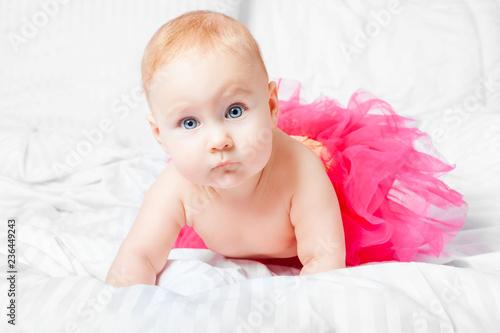 Fototapeta Cute baby girl in pink skirt with blue eyes over white blanket. obraz
