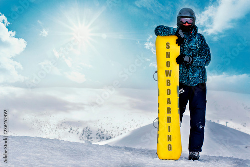 Snowboarder portrait with snowboard on mountain top. Snowboarding on ski resort