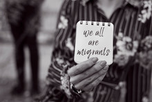 Woman And Note With The Text We All Are Migrants