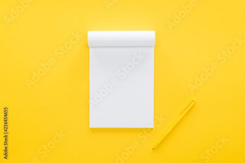 Obraz top view of blank notebook on yellow background - fototapety do salonu