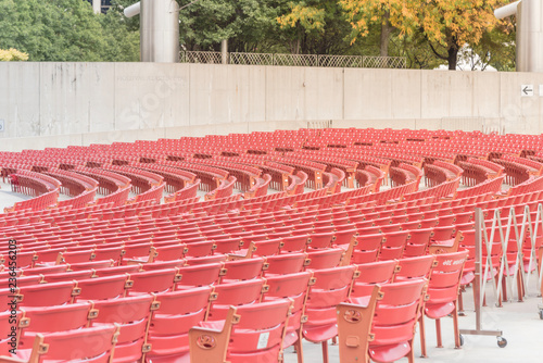 Fotobehang Theater Line of raised orchestra level seats from public outdoor performing art venue in Chicago. Fall foliage color in background