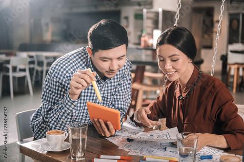 Fotografía  Helpful beautiful wife joining her husband preparing for presentation