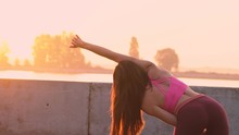 Young Athletic Girl Doing Gymnastic Exercises On The Beach. A Woman Makes A Bend To The Side. Shooting Medium Plan. Pink Sunset Sky. Slow Motion.