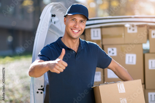 Fotografie, Obraz  Delivery man standing in front of his van