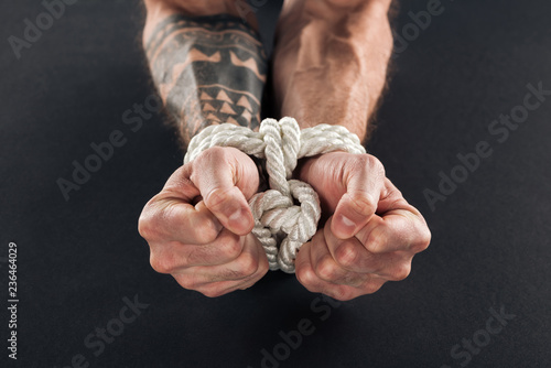 cropped view of male hands bound with rope isolated on black Canvas Print